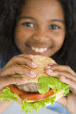 Jong meisje dat cheeseburger het glimlachen eet Stock Afbeeldingen