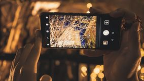 Jong meisje dat een beeld met haar telefoon neemt aan een restaurant bij nacht stock afbeeldingen
