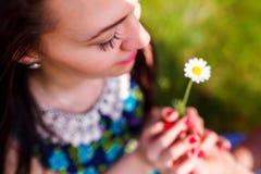 Jong meisje dat een bloem ruikt Stock Foto