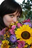Jong meisje dat een bos van bloemen houdt stock afbeeldingen
