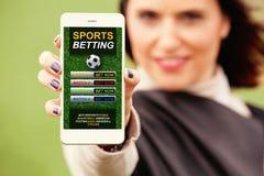 Jong meisje dat een cellphone met sporten houdt die app in het scherm wedden stock fotografie