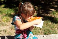 Jong meisje dat een plak van kaaspizza buiten eet Royalty-vrije Stock Foto's