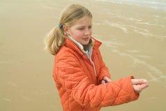 Jong meisje dat een vlieger op het strand vliegt Stock Foto