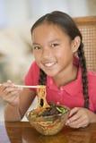 Jong meisje dat in eetkamer Chinees voedsel eet Royalty-vrije Stock Fotografie
