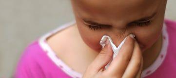 Jong meisje dat haar neus blaast Stock Afbeeldingen