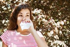Jong meisje dat haar neus blaast Jong meisje met allergie in de herfstpark stock afbeeldingen