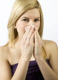 Jong meisje dat haar neus met een zakdoek schoonmaakt Stock Afbeelding
