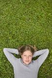 Jong meisje dat in het gras ligt dat droomt van? Stock Afbeeldingen