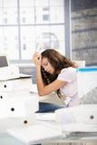 Jong meisje dat hoofdpijn in bureau heeft Royalty-vrije Stock Fotografie