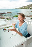 Jong meisje dat koffiepauze in oceaanmeningskoffie heeft Stock Fotografie