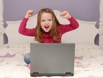 Jong meisje dat laptop met behulp van stock foto's