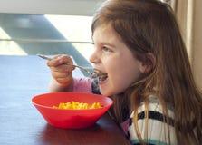 Jong meisje dat macaroni en kaas eet stock afbeeldingen