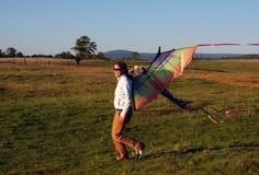 Jong meisje dat met vlieger loopt stock afbeeldingen