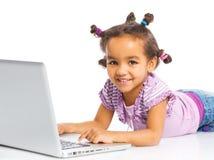 Jong meisje dat notitieboekjecomputer met behulp van Stock Afbeelding