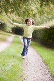Jong meisje dat op een weg loopt die in openlucht glimlacht royalty-vrije stock afbeelding