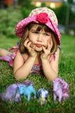Jong meisje dat op gras, dat hoofd houdt in handen ligt Stock Foto's