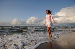 Jong meisje dat op het strand overslaat Stock Foto