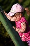 Jong meisje dat op omheining beklimt Stock Foto's