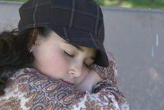 Jong meisje dat op parkbank rust Stock Foto