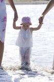 Jong meisje dat op strand door ouders wordt gelopen Stock Foto's