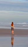 Jong meisje dat op strand loopt Stock Foto's