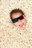 Jong meisje dat in popcorn wordt begraven Stock Foto's