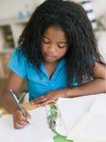 Jong Meisje dat Thuiswerk doet Stock Afbeelding