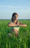 Jong meisje dat yoga doet tegen aard stock fotografie