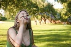 Jong meisje dat zeepbels opblaast Stock Foto's