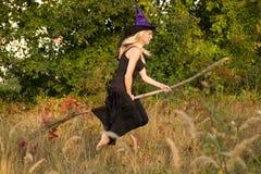 Jong meisje in de vliegen van het heksenkostuum op bezemsteel Stock Afbeelding