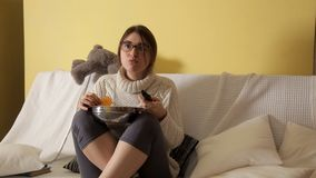Jong meisje in de winteravond thuis in een witte sweater op de laag die glazen dragen, op TV letten en spaanders eten stock video