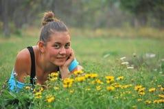 Jong meisje dichtbij gele bloemen royalty-vrije stock afbeeldingen