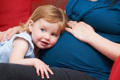 Jong Meisje die aan de Buik van de Zwangere Moeder luisteren stock foto's
