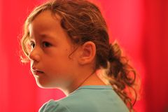 Jong Meisje die aan de Kant op Rode Achtergrond kijken Royalty-vrije Stock Afbeelding