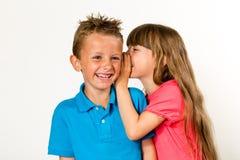 Jong meisje die aan jonge jongen fluisteren stock afbeeldingen