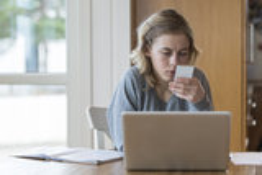 Jong meisje die aan laptop en een telefoon werken Royalty-vrije Stock Afbeelding