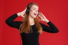 Jong meisje die, die aan muziek luisteren en in hoofdtelefoons zingen Op een rode achtergrond stock afbeelding