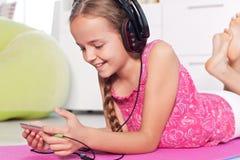 Jong meisje die aan muziek op haar smartphone luisteren die - op F liggen Stock Fotografie