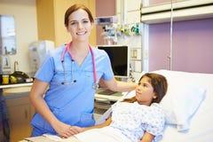 Jong Meisje die aan Vrouwelijke Verpleegster In Hospital Room spreken royalty-vrije stock foto