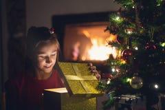 Jong meisje die aangezien zij een gouden giftbox opent glimlachen royalty-vrije stock afbeelding