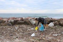 Jong Meisje die Afval van het Strand opnemen stock afbeelding