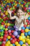 Jong meisje die in balkuil gekleurde ballen werpen stock fotografie