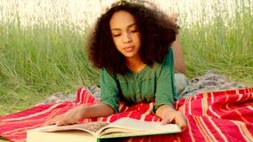 Jong meisje die bij dekking en het lezen liggen stock video