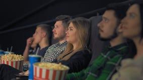 Jong meisje die, blond, op een film in de bioskoop letten, en o.k. tonen stock videobeelden