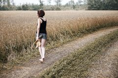 Jong meisje die blootvoets op de grondweg door gebied en bos lopen, het concept de zomer en reis stock afbeeldingen
