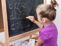 Jong meisje die brieven op bord leren te schrijven royalty-vrije stock afbeeldingen