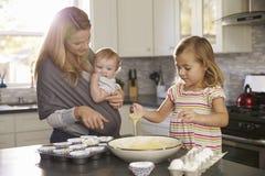 Jong meisje die cakemengeling in keuken voorbereiden, mum tonend baby stock foto's