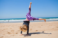 Jong meisje die cartwheel bij strand doen Royalty-vrije Stock Foto's