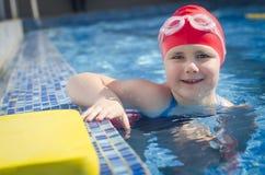 Jong meisje die in de pool met schuimraad leren te zwemmen Stock Afbeelding