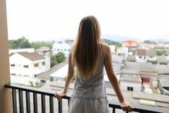 Jong meisje die de zomerpyjama's dragen die zich op balkon bevinden en gebouwen op achtergrond bekijken Royalty-vrije Stock Fotografie